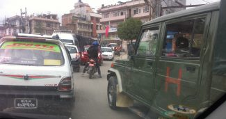 Red car followed by a motorcyle & army jeep-feat image